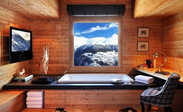 Баня с вана и дървени облицовки на стените